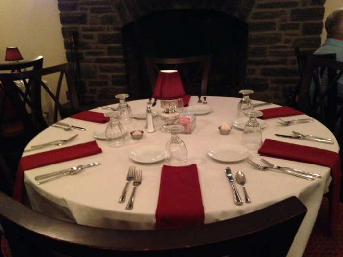 A table for six in front of the fireplace at Revere Tavern