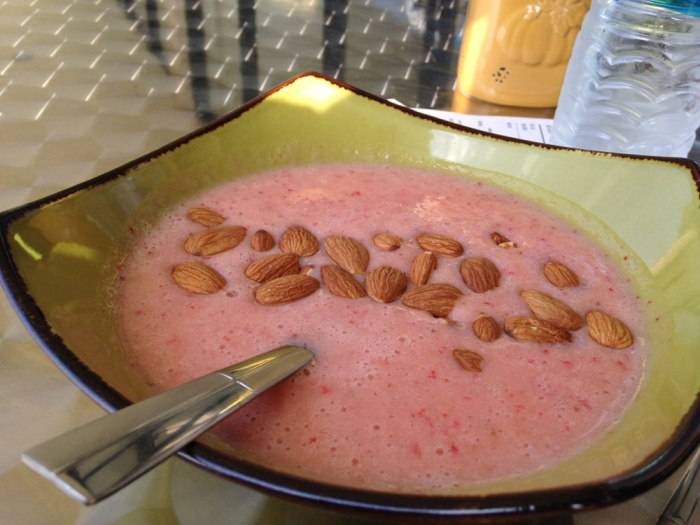 A strawberry-orange smoothie bowl with almond milk and sliced almonds.